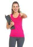 与剪贴板的微笑的健身教练员指向秘密审议的 库存照片