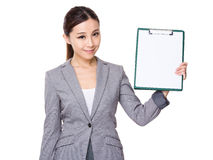 与剪贴板whtie纸的女实业家展示  免版税库存图片