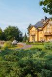 与割断的树的一个美丽的豪宅与胡同由bruschatka、古老灯笼和花床做成 库存照片
