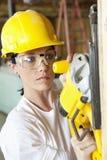 与力量的严肃的女性建筑工人切口木头看见了 免版税库存照片