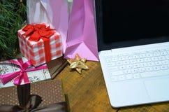 与办公室桌的Cristmas背景与开放膝上型计算机,礼物盒 企业假日概念 网络购物为 免版税库存照片