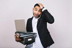 与办公室箱子,文件夹,膝上型计算机的画象勤勉attaractive商人谈话在白色背景的电话 免版税库存图片