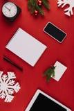 与办公用品、装饰雪花和在红色隔绝的圣诞节玩具的平的位置 库存图片