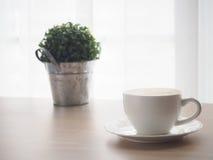 与加奶咖啡杯子的木桌拿铁咖啡,小树雀鳝 库存图片