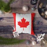 与加拿大旗子的新年快乐标记在枕头 在木桌上的圣诞装饰概念与可爱的对象 免版税库存图片