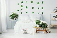 与加长型的床、都市密林和绿色叶子的白色卧室内部在墙壁上 库存照片
