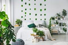 与加长型的床与枕头和毯子,都市密林和绿色叶子的白色卧室内部在墙壁上 免版税库存照片