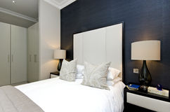 与加长型的床的当代卧室细节与豪华desig 免版税库存图片