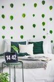 与加长型的床的白色卧室内部,在墙壁上的都市密林绿色叶子和在咖啡桌上的小膝上型计算机 库存图片