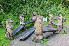 与动物木雕塑的长凳在terrenkur健康的沿Belokurikha山河落后 免版税库存照片