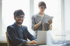 与助理的成功的商人在工作在办公室 库存图片