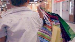 与包裹的顾客孩子到手里通过购物中心追捕在时尚精品店的购买 股票视频