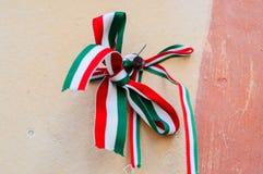 与匈牙利的全国颜色的丝带栓了由oldcastle墙壁决定在穆卡切沃,乌克兰 全国记忆天概念 图库摄影