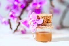 与化妆奶油、胶凝体和紫色兰花的温泉设置在白色木桌背景 库存图片