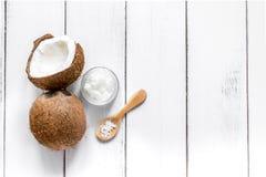 与化妆油的新鲜的椰子在白色背景顶视图的瓶子 库存照片
