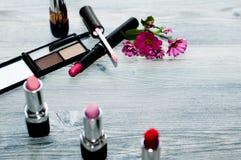 与化妆瓶和花的秀丽平的位置 顶视图 免版税库存照片