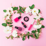 与化妆用品、唇膏、眼影、指甲油和花卉框架的秀丽构成在桃红色背景 平的位置,顶视图 库存照片