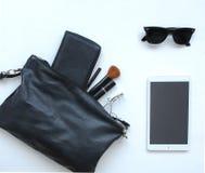 与化妆用品、太阳镜和片剂的女性袋子 免版税库存图片