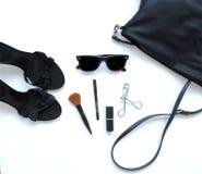 与化妆用品、太阳镜和鞋子的女性袋子 免版税库存图片