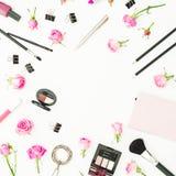 与化妆用品、辅助部件和桃红色玫瑰的工作区在白色背景 顶视图 平的位置 秀丽博克背景 图库摄影