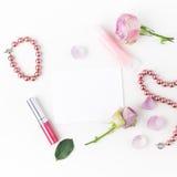 与化妆用品和桃红色玫瑰的平的位置构成开花 顶视图 免版税库存照片