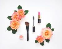 与化妆用品和玫瑰色花的装饰构成 顶视图,平的位置 免版税库存图片