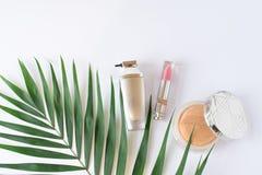 与化妆用品和绿色热带叶子的装饰平的被放置的构成 平的位置,在白色背景的顶视图 免版税库存图片