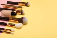 与化妆美容品的专业构成产品,脸红,眼睛划线员、眼睛鞭子、刷子和工具在桃红色和黄色 免版税库存图片