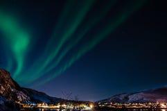 与北极光(极光)的夜空在挪威海湾 图库摄影