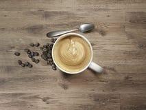 与匙子和咖啡豆的热奶咖啡在木表上 库存图片