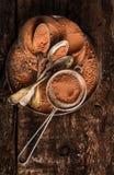 与匙子和过滤器的巧克力粉末在黑暗的木背景 免版税库存图片