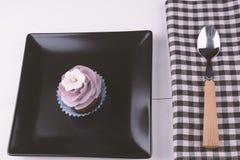 与匙子和餐巾的杯形蛋糕 库存照片