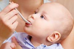 与匙子的母亲哺养的婴孩婴儿食品 免版税图库摄影