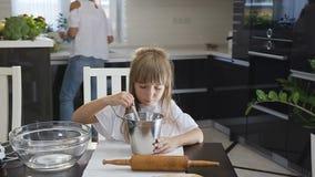 与匙子的特写镜头小女孩混合的面粉,当烹调面团时,当她的妈妈是繁忙的在厨房里时 小俏丽的女孩 股票录像