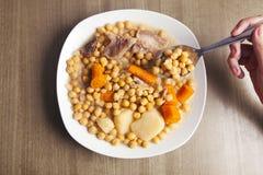 与匙子的鸡豆炖煮的食物和手 库存照片