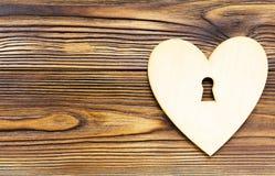 与匙孔的木心脏在与拷贝空间的木背景 图库摄影