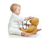 与医生和玩具熊衣裳的可爱的孩子  库存图片