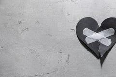 与医疗膏药的被撕毁的纸心脏 库存照片