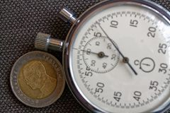 与十在棕色牛仔裤背景-企业背景的泰铢(后部)和秒表的衡量单位的泰国硬币 免版税库存图片