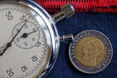 与十在深蓝牛仔布的泰铢(后部)和秒表的衡量单位的泰国硬币与红色条纹背景-企业backgro 免版税库存图片