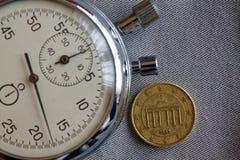 与十在灰色牛仔布背景-企业背景的欧分(后部)和秒表的衡量单位的欧洲硬币 免版税库存照片