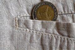 与十在破旧的亚麻布裤子的口袋的泰铢的衡量单位的泰国硬币 免版税图库摄影