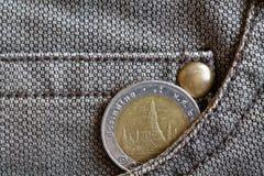 与十在破旧的棕色牛仔布牛仔裤的口袋的泰铢的衡量单位的泰国硬币 免版税库存照片