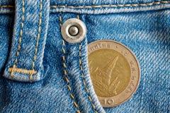 与十在破旧的浅兰的牛仔布牛仔裤的口袋的泰铢的衡量单位的泰国硬币 库存图片