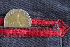 与十在破旧的蓝色牛仔布牛仔裤的口袋的泰铢的衡量单位的泰国硬币有红色条纹的 免版税库存照片