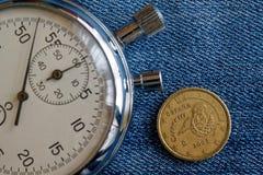 与十在破旧的蓝色牛仔布背景-企业背景的欧分(后部)和秒表的衡量单位的欧洲硬币 库存照片