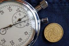 与十在破旧的蓝色牛仔裤背景-企业背景的欧分(后部)和秒表的衡量单位的欧洲硬币 库存照片