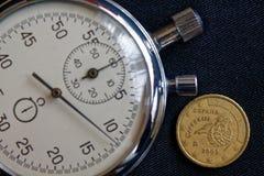 与十在破旧的黑牛仔布背景-企业背景的欧分(后部)和秒表的衡量单位的欧洲硬币 图库摄影