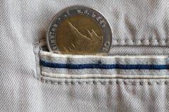 与十在米黄牛仔布牛仔裤的口袋的泰铢的衡量单位的泰国硬币有蓝色条纹的 库存图片