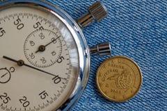 与十在蓝色牛仔布背景-企业背景的欧分(后部)和秒表的衡量单位的欧洲硬币 免版税图库摄影